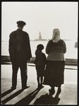 A young boy points out the Statue to his immigrant parents from Ellis Island.