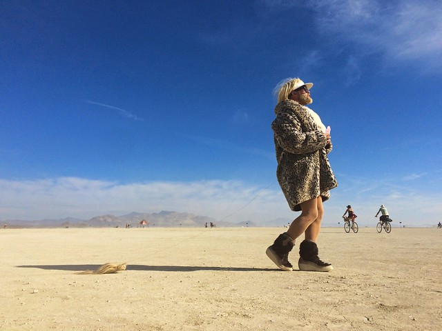 A festivalgoer at Burning Man paces across the desert. Photo by Kevin Cheng
