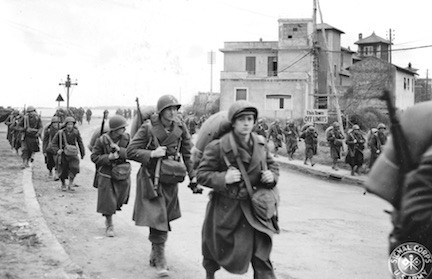 U.S. 45th Infantry Division soldiers march through Anzio on their way to the front.