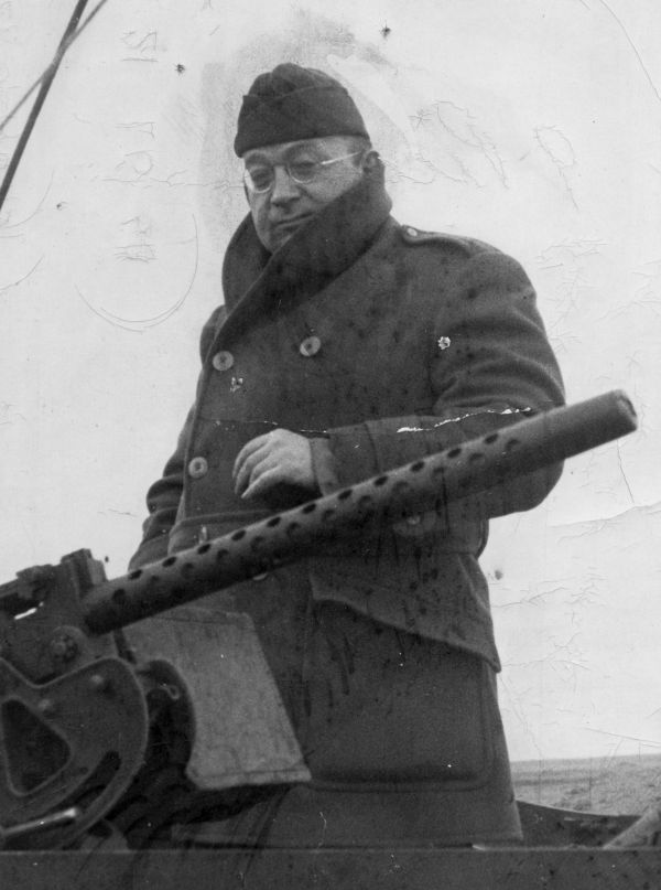 New Yorker writer A.J. Liebling stands beside a machine gun during World War II. Cornell University Library.