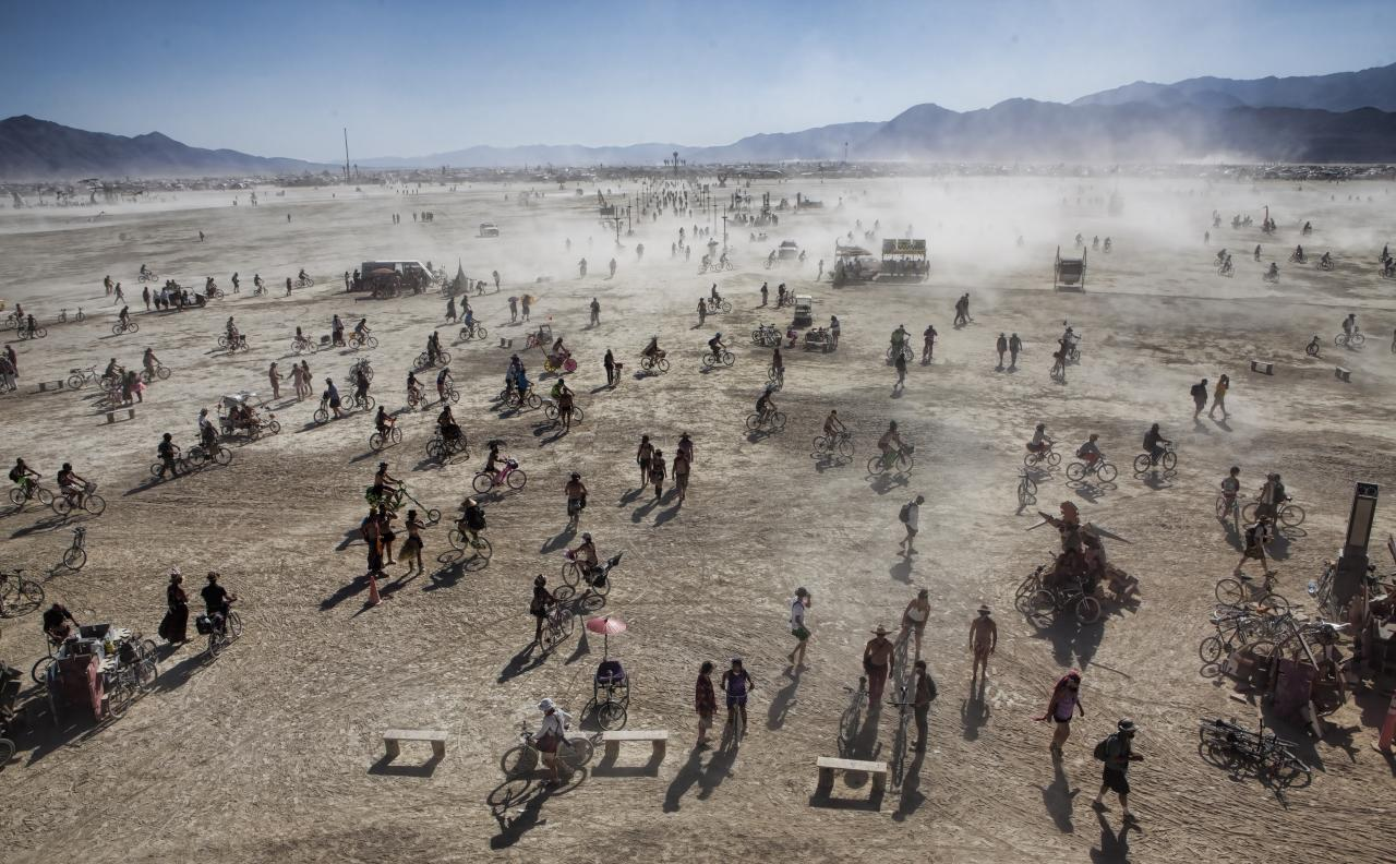 Festival goers kick up dust at Burning Man. Photo by Christopher Michel