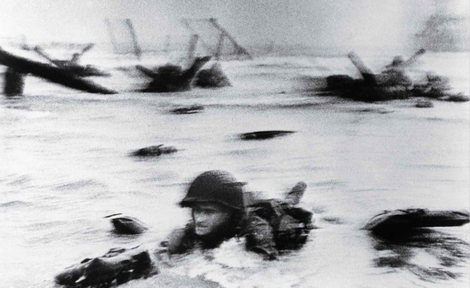 LCIL-88 carried an elite band of Navy demolitionists to Normandy to clear the obstacles that Germans had planted to repel an attack on Omaha Beach, some of which could be seen in Robert Capa's famous photograph of a soldier wading ashore. Library of Congress.