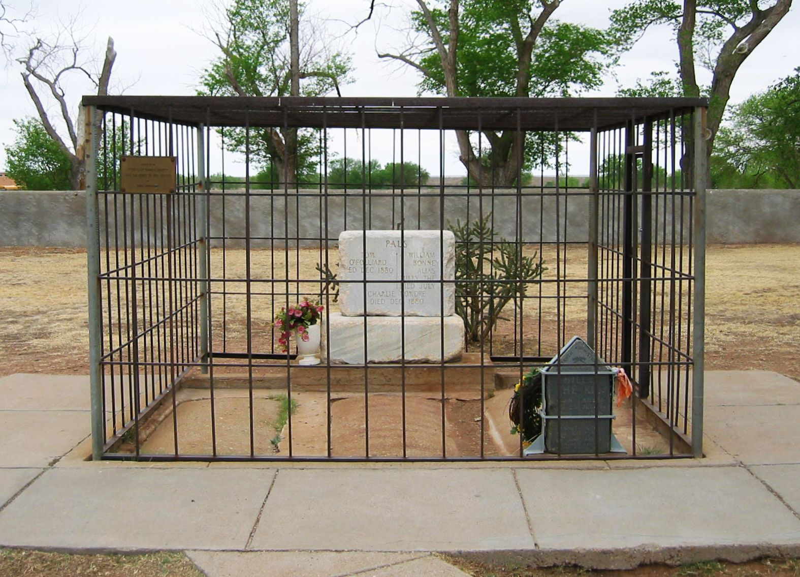 Finally caged in death: Billy the Kid is reportedly buried under a tombstone at the Old Fort Sumner Cemetery is enclosed behind iron bars to prevent it being stolen for a third time.  Photo by Sam Vast.
