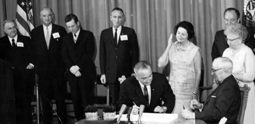 President Lyndon Johnson signed the Medicare Bill in 1965 at the Harry Truman Library as the former President and his wife Bess looked on.