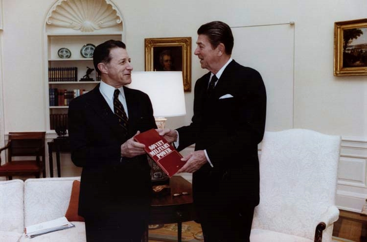 U.S. Secretary of Defense Caspar Weinberger presents President Ronald Reagan with the debut edition of Soviet Military Power, a flagship Defense Intelligence Agency (DIA) publication. Photo Courtesy of Wikimedia Commons.