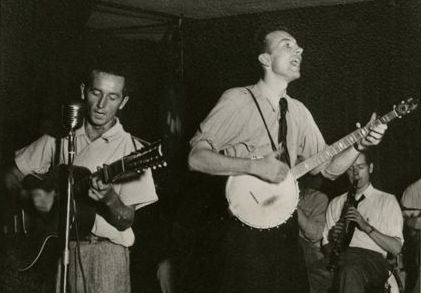 "Pete Seeger modified ""We Shall Overcome,"" and sang frequently with Woody Guthrie (left)."