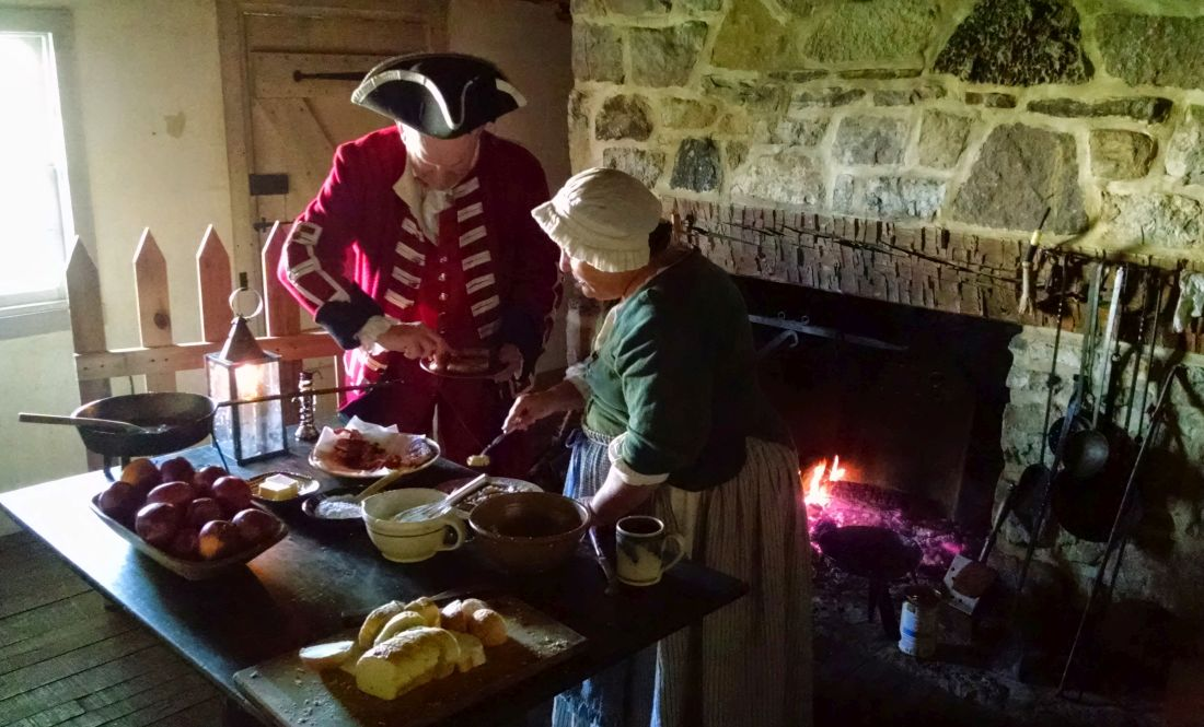 Reenactors enjoy a breakfast of ham and French toast cooked over a fireplace.